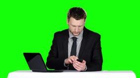 Geschäftsmann, der an einem Schreibtisch sitzt und Notizbuch verwendet und um das Telefon ersucht Grüner Bildschirm stock video