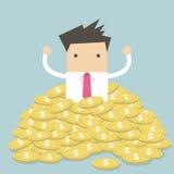 Geschäftsmann, der in einem Stapel von Goldmünzen sitzt Stockbild