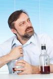 Geschäftsmann, der an einem Tisch mit einer Flasche sitzt Lizenzfreies Stockfoto