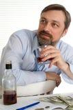 Geschäftsmann, der an einem Tisch mit einer Flasche sitzt Lizenzfreie Stockfotografie