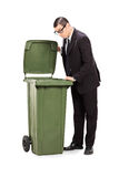 Geschäftsmann, der einen Abfalleimer untersucht Stockbilder