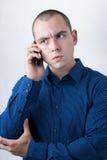 Geschäftsmann, der einen Anruf mit ernstem Gesichtsausdruck macht Stockbilder