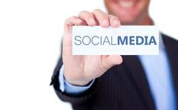 Geschäftsmann, der einen Aufkleber mit den Sozialmedien geschrieben auf ihn hält Lizenzfreie Stockfotos