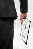 Geschäftsmann, der einen Berührungsflächen-PC mit einer Zeitung anhält Stockbild