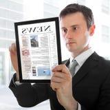 Geschäftsmann, der einen Berührungsflächen-PC mit Ezeitung anhält Lizenzfreie Stockfotografie