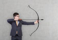 Geschäftsmann, der einen Bogen hält Lizenzfreie Stockbilder