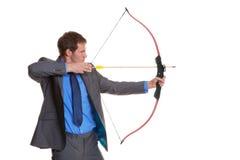 Geschäftsmann, der einen Bogen und einen Pfeil schießt Stockfotos