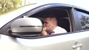 Geschäftsmann, der einen Burger sitzt im Auto isst stock video footage