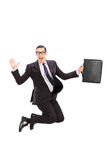 Geschäftsmann, der einen Fall hält und in die Luft springt Lizenzfreie Stockbilder
