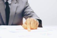 Geschäftsmann, der einen Finger auf Diagrammdokument zeigt Lizenzfreies Stockfoto
