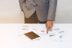 Geschäftsmann, der einen Finger auf Diagrammdokument zeigt Stockbilder