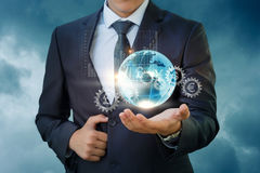 Geschäftsmann, der einen globalen Finanzmarkt hält Stockbild