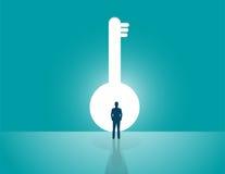 Geschäftsmann, der einen großen Schlüssel schaut Stockbild