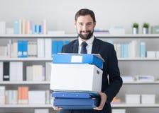 Geschäftsmann, der einen Kasten und Büroordner trägt stockbild