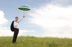 Geschäftsmann, der einen Regenschirm anhält Stockfoto