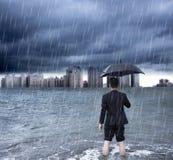 Geschäftsmann, der einen Regenschirm und eine Stellung mit Wolkenbruch hält Lizenzfreie Stockfotografie