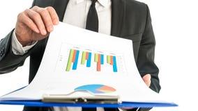 Geschäftsmann, der einen Satz Diagramme analysiert und eine Karte mit sta hält Lizenzfreie Stockfotos