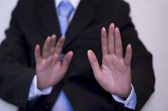 Geschäftsmann, der einen schwarzen Anzug, beide Hände anhebend, Hintergrundstadtlandschaft, Korruptionsbekämpfungs- Konzept trägt stockfotografie