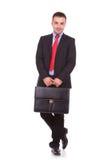 Geschäftsmann, der einen schwarzen ledernen Aktenkoffer hält Lizenzfreie Stockfotografie