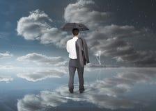 Geschäftsmann, der einen schwarzen Regenschirm hält Lizenzfreie Stockfotografie