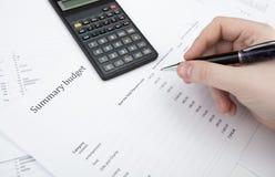 Geschäftsmann, der einen Stift und Zählungen das Budget hält Stockfoto