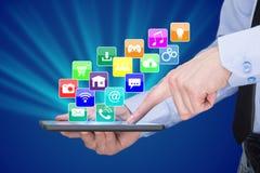 Geschäftsmann, der einen Tabletten-PC mit beweglichen Anwendungsikonen auf virtuellem Schirm hält Internet und Geschäftskonzept Lizenzfreie Stockfotos