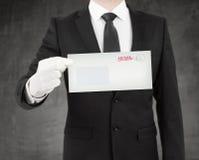 Geschäftsmann, der einen Umschlag gibt Stockfotos