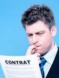 Geschäftsmann, der einen Vertrag liest Lizenzfreies Stockbild