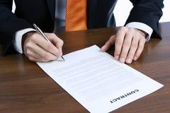 Geschäftsmann, der einen Vertrag unterzeichnet Stockfotografie