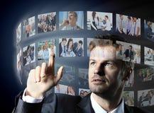Geschäftsmann, der einen virtuellen Knopf bedrängt Stockbild