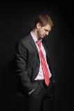 Geschäftsmann, der in einer Freistellung, sein Kopf gebeugt sitzt. Stockfotos