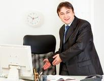 Geschäftsmann, der einlädt, um auf Bürostuhl zu sitzen Lizenzfreies Stockbild