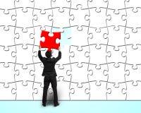 Geschäftsmann, der einzigartiges rotes Puzzlespiel zur weißen Puzzlespielwand zusammenbaut Stockfotos