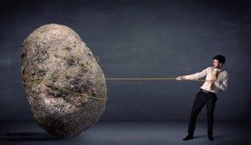 Geschäftsmann, der enormen Felsen mit einem Seil zieht Stockfotos