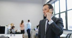 Geschäftsmann, der Entscheidungen während des Telefonanrufs im modernen Büro trifft, während Gruppe Geschäftsleute auf Sitzung te