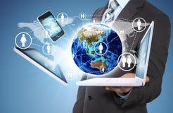 Geschäftsmann, der Erde und Elektronik hält Lizenzfreie Stockbilder