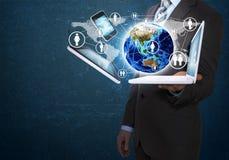 Geschäftsmann, der Erde und Elektronik hält Lizenzfreie Stockfotografie