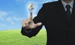 Geschäftsmann, der Erdkugel in der Glühlampe über grünem Gras bedrängt Stockbilder