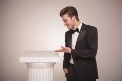 Geschäftsmann, der etwas auf einer weißen Spalte darstellt Lizenzfreies Stockbild