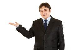 Geschäftsmann, der etwas auf leerer Hand darstellt Lizenzfreie Stockfotografie