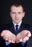 Geschäftsmann, der etwas auf seiner Hand über Grau darstellt Stockfotografie