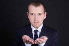 Geschäftsmann, der etwas auf seiner Hand darstellt Lizenzfreie Stockfotos