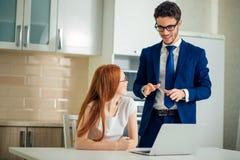 Geschäftsmann, der etwas Frau mit Laptop erklärt Lizenzfreies Stockfoto