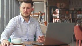 Geschäftsmann, der etwas Papiere auf das Café betrachtet stock footage