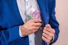 Geschäftsmann, der 500 Eurobanknoten von seiner Jacke entfernt Lizenzfreie Stockfotografie