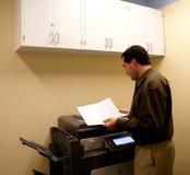 Geschäftsmann an der Exemplarmaschine lizenzfreie stockbilder