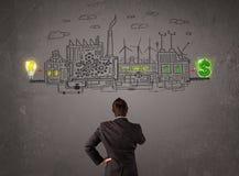Geschäftsmann, der Fabrik betrachtet, die Geld von den Ideen verdient Lizenzfreies Stockbild