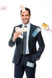 Geschäftsmann, der in fallendem Geld lächelt Stockfoto