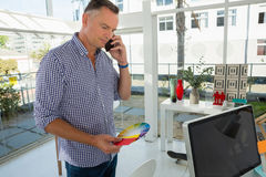 Geschäftsmann, der Farbmuster bei der Unterhaltung am Handy hält Lizenzfreies Stockfoto