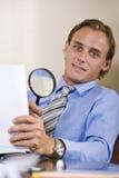 Geschäftsmann, der feinen Druck im Vertrag liest Stockfoto
